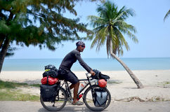 Thai man riding bicycle on road near Thung Wua Laen Beach stock images