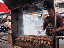 Thai man selling food in the streets of Nakhon Ratchasima. NAKHON RATCHASIMA, THAILAND - CIRCA APRIL, 2014: Thai man selling Khao Moo Ping (Thai Grilled Pork on Stock Images