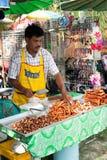 Thai man selling fried pork meat at market. Phuket, Thailand. PHUKET, THAILAND - MARCH 01: Thai man selling fried pork meat at market on March 01, 2013 at Phuket Royalty Free Stock Photos