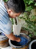 Thai men tie batik dyeing Indigenous Knowledge chemical and liquid dye Mauhom and indigo color in pot at Nonthaburi, Thailand. Thai man tie batik dyeing stock photos