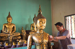 Thai man try to patch a golden  foil at the statue of Buddha in temple Stock Photos