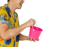 Thai man with white clay filler on his face holding Bucket for Songkran festival. Asian Thai man with white clay filler on his face holding pink Bucket or Pail stock photography