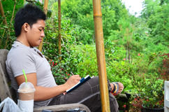 Thai man writing memory on book in the garden Royalty Free Stock Photography