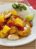 Thai mango chicken. Spicy Thai mango chicken with red peppers and rice served on a white plate Royalty Free Stock Photo