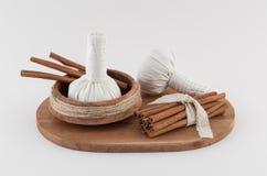 Thai Massage Balls and Cinnamon. Aromatic Thai spa massage balls and cinnamon sticks on natural wooden tray Stock Images