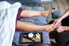 Thai massage at foot in spa. Thai massage by lotion at foot to Asianwoman on sofa bed in spa salon. Health care and Relax to heal pain concept Stock Photo