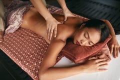 thai massage Kvinna som har avkopplingbaksidamassage på den Spa salongen royaltyfri foto