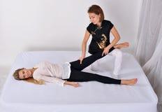 thai massage Massageterapeut som arbetar med kvinnan Arkivbild
