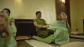 Thai massage at spa. Two young pretty women getting thai massage at spa stock footage