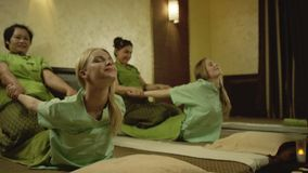 Thai massage at spa. Two young pretty women getting thai massage at spa stock video footage