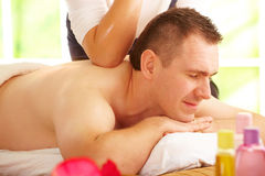 Thai massage treatment. Male enjoying kind of Thai massage treatment with female hand on back Royalty Free Stock Image