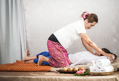 Thai Masseuse doing massage for woman in spa salon. Asian beautiful woman getting thai herbal massage compress massage in spa.She Stock Photos