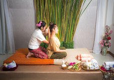 Thai Masseuse doing massage for woman in spa salon. Asian beautiful woman getting thai herbal massage compress massage in spa.She Stock Photo