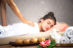 Thai Masseuse doing massage for woman in spa salon. Asian beautiful woman getting thai herbal massage compress massage in spa.She Royalty Free Stock Image