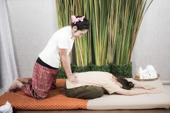 Thai Masseuse doing massage for woman in spa salon. Asian beautiful woman getting thai herbal massage compress massage in spa Royalty Free Stock Images