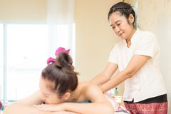 Thai Massuer is pampering customer in Thai Spa, Focus on the Therapist Stock Image