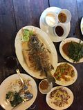 Thai meal in a restaurant. Which consist of fish, stinky beans, water spinach, mango salad which are all cooked in traditional Thai style stock photos