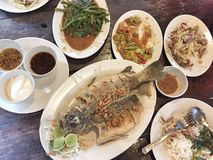Thai meal in a restaurant. Which consist of fish, stinky beans, water spinach, mango salad which are all cooked in traditional Thai style royalty free stock photo