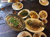 Thai meal in a restaurant. Which consist of fish, stinky beans, water spinach, mango salad which are all cooked in traditional Thai style stock photo