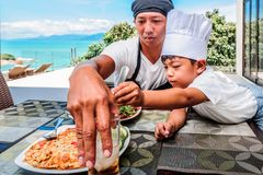 Thai man and his cute son having lunch at home. Playing game of cooks: apron, chef`s hat and thai food royalty free stock photo