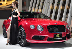 Thai model stands next to a Bentley convertible Royalty Free Stock Photography