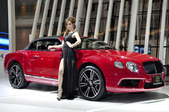Thai model stands next to a Bentley convertible Royalty Free Stock Image