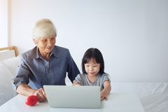 Thai modern grandmother and her little granddaughter sitting and royalty free stock image