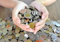 Thai Money in the hands of the girl. Many Thai coins in the hands of young women.To use to pay.on wooden table royalty free stock photo