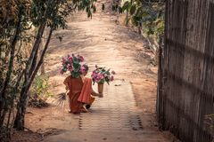 Thai monk with lotus flowers in his hands and traditional broom Stock Photo