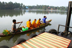 Thai monk paddle the boat receiving food on canal Royalty Free Stock Photos