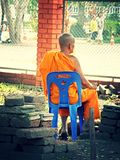 Thai monk sitting on a chair. Royalty Free Stock Photography