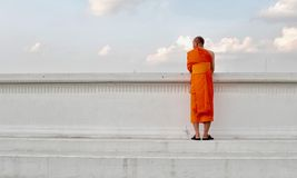 Thai monk stands by the side of the river. An old man who is also a Thai monk, stands by the side of a river under blue skies. He appears to be deep in thought Stock Image