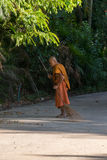 Thai monk sweeping a temple floor Royalty Free Stock Photography