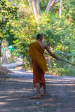 Thai monk sweeping a temple floor Royalty Free Stock Images