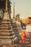 Thai monk is walking in front of old ancient pagoda at Wat Pho Temple in Bankgok, Thailand. royalty free stock images