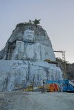Thai monks looking at large statue of Buddha on the cliff. Suphanburi, Thailand - November 29, 2015: Thai monks look at large statue of Buddha being built on the Royalty Free Stock Photography