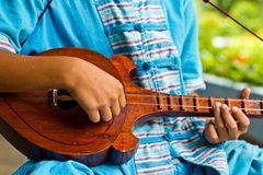 Thai music instrument. The boy plays a local Thai music instrument Stock Images