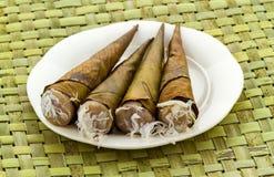 "Thai native dessert called "" Kanom Kruay""in white dish on Zigzag interlocking of coconut leaves Royalty Free Stock Images"