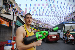Thai New Year - Songkran. A reveller poses with a water-gun while  celebrating the Thai New Year near Khao San Road on April 12, 2013 in Bangkok, Thailand. The Stock Photography