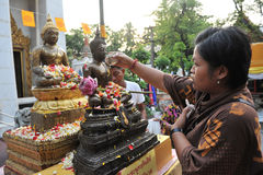 Thai New Year - Songkran. A woman pours water over a Buddha statue at a temple while taking part in traditional celebration of the Thai New Year on April 12 stock image
