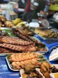 Thai night market with national food: fried fish, sushi, rice sweets, skewers, sushi, seafood stock photo