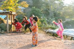 Thai northern kid wearing pyjamas standing with sunlight and her friends in the background in the Akha village of Maejantai. Thai northern kid wearing pyjamas royalty free stock photo
