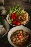 Thai Northern Style Pork and Tomato Chili Relish, nam prik ong in white bowl on wood table there are side dishes of fresh. Vegetables, cooked rice and flower royalty free stock photos