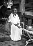 Thai nun sat on the part of the wooden bridge collecting offerings Stock Photography