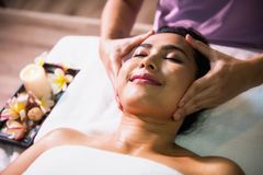 Thai oil massage at face. Happy Asian beautiful woman relax in spa club. Body care treatment by Thai oil. Cute girl massage at face by professional massager royalty free stock photography