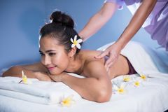 Thai oil massage to Asian girl in spa. Attractive happy Asian beautiful woman relax in spa. Body care treatment. Cute female having massage at back by stock images