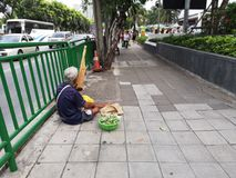 Thai old man sits by the roadside and plays music with sell the key chain for tourists and Thai people to make money,ratchadapisek royalty free stock image