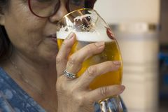 Thai old woman drinking beer czech style. In glass on table of restaurant in Prague, Czech Republic royalty free stock image