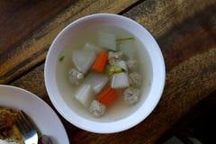 Thai ord för Tom Gaeng Jued Look Chin mu, klar glass nudelsoppa, klar soppa med Bean Curd och finhackat griskött, klar soppa med  royaltyfri fotografi