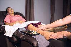 Thai original massage foot spa. Thai original massage to beautiful Asian woman on sofa. Foot and leg spa treatment. Health care and Relax  concept Royalty Free Stock Images
